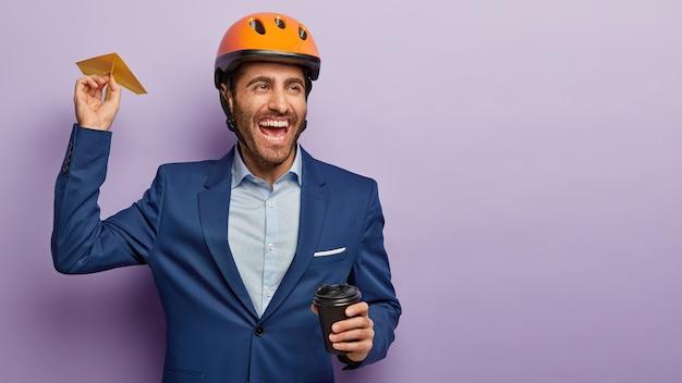 Immagine di felice ingegnere maschio spensierato lancia un aereo fatto a mano, beve caffè, felice di raggiungere il successo sul lavoro, guarda lontano e ride