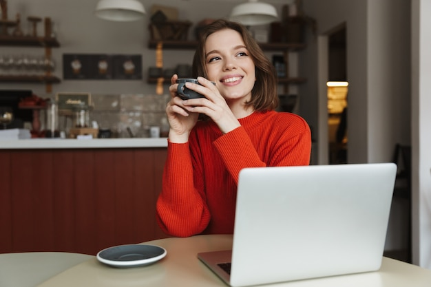 Image of happy caucasian woman 20s smiling, while using laptop and drinking coffee in cafe
