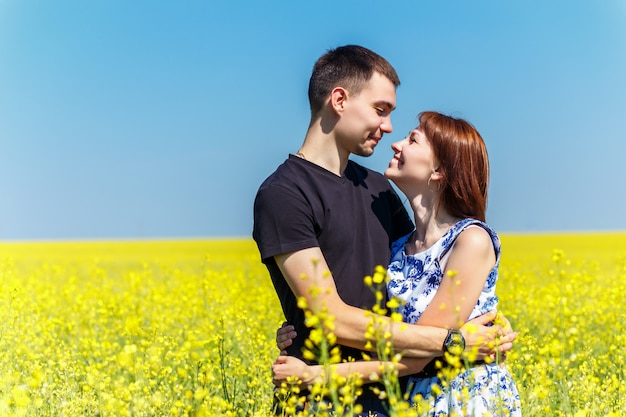 Image of happy couple embracing in yellow meadow