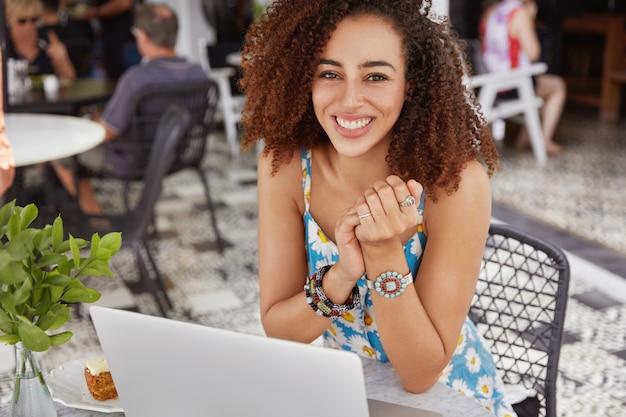 L'immagine della giovane femmina dalla pelle scura felice con stile di capelli afro, ha un'espressione positiva