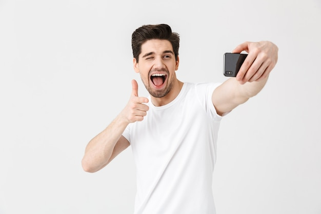 Image of happy emotional young man posing isolated over white wall  pointing take selfie by mobile phone.
