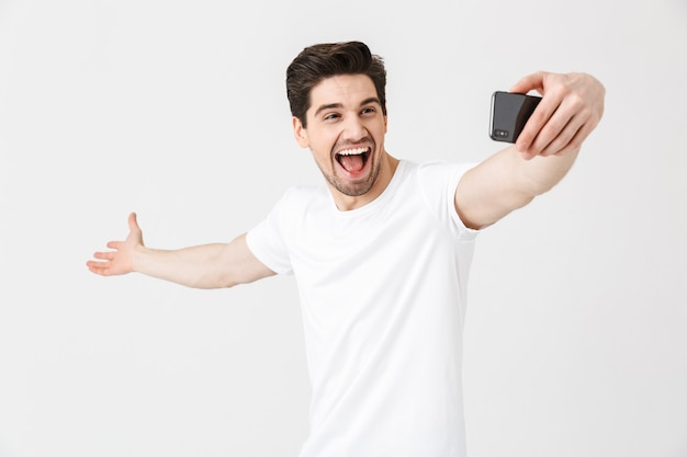 Image of happy emotional young man posing isolated over white wall  take selfie by mobile phone.