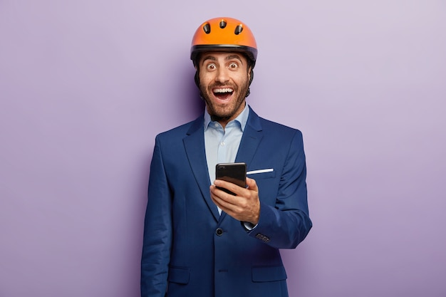 Image of happy engineer holds mobile phone, sends text messages to colleagues, wears orange helmet and elegant suit