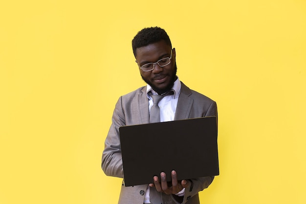 An image of happy excited young african man isolated over yellow wall using laptop computer.