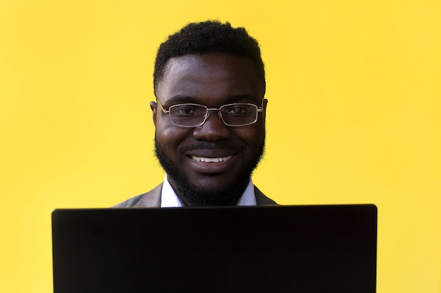An image of happy excited young man isolated over yellow wall using laptop computer.