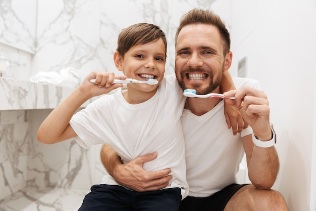 Image of happy father and son smiling, and cleaning teeth together in bathroom