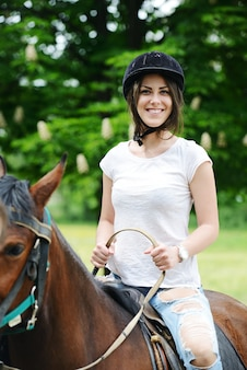 Image of happy female sitting on horse at village farm