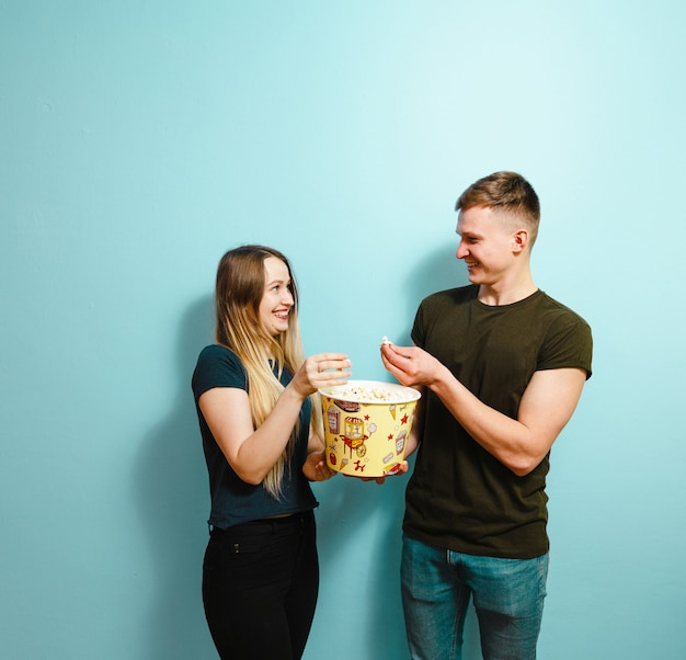 Image of happy  friends isolated holding pop corn watch film.