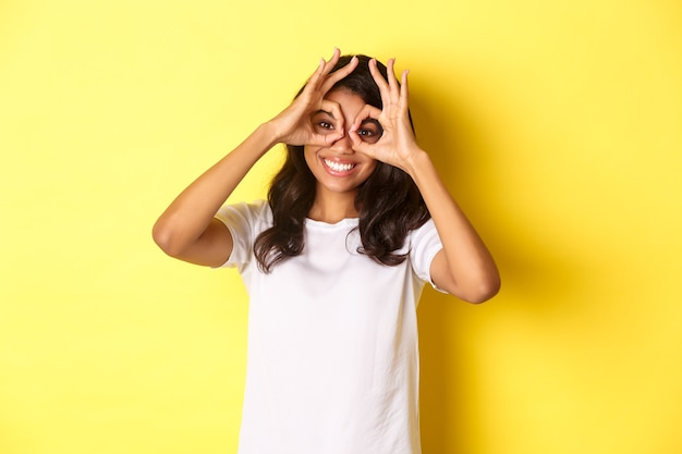 Image of happy and funny africanamerican girl making finger glasses and looking through them standin...
