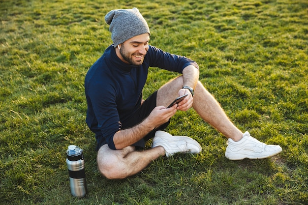Image of a happy handsome young strong sports man wearing hat posing outdoors at the nature park location resting sitting listening music with earphones using phone.