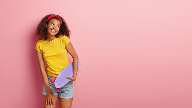 Image of happy lovely teenage girl with curly hair posing in yellow tshirt