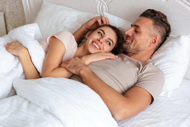 Image of happy loving couple lying together on bed at home