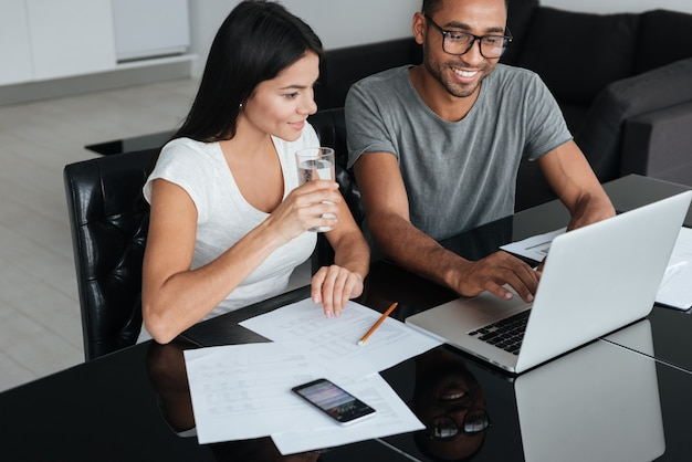 Image of happy loving young couple using laptop and analyzing their finances with documents. look at laptop.
