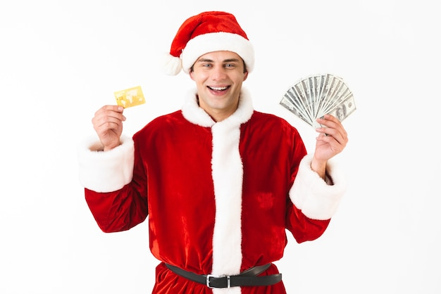 Image of happy man 30s in santa claus costume holding dollar bills and credit card