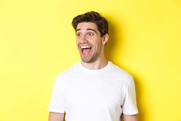 Immagine di un uomo felice che controlla la promozione, che guarda a sinistra con stupore, in piedi con una maglietta bianca su sfondo giallo