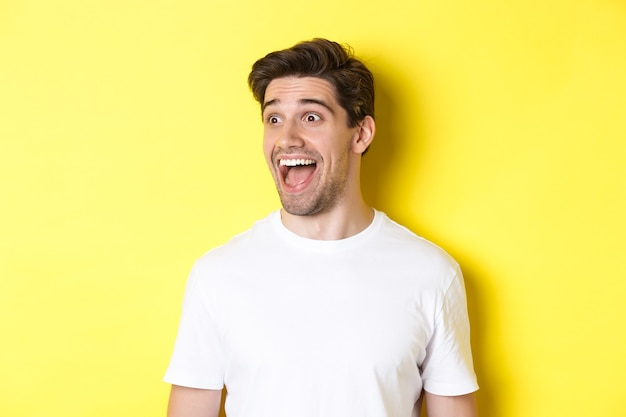 Image of happy man checking out promo, looking left with amazement, standing in white t-shirt against yellow background.