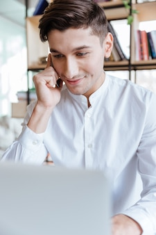 Image of happy man dressed in white shirt using laptop computer while talking by phone. coworking. look aside.