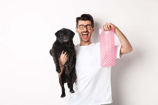 Image of happy man, pet owner, holding cute black pug and dog poop bag, standing over white