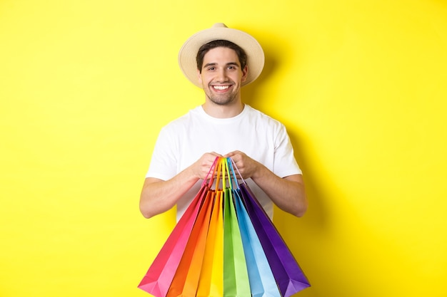 Image of happy man shopping on vacation, holding paper bags and smiling, standing against yellow background.
