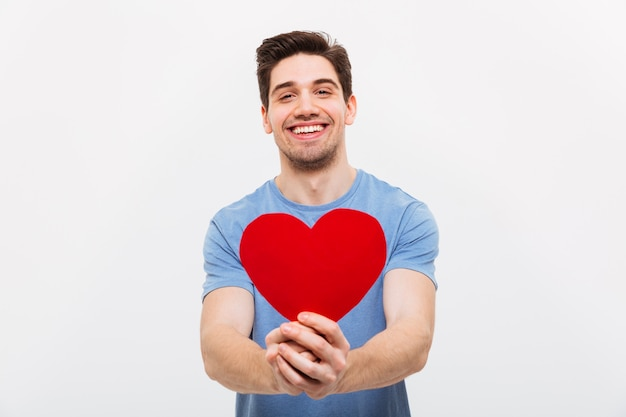 Image of happy man in t-shirt giving paper heart