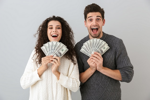 Image of happy man and woman holding fan of dollar money, isolated over gray wall