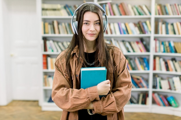Image of happy nice girl in casual wear, using headphones and listening to music, holding blue book in hands, while standing against bookcases space in college library