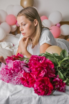 Image of a happy positive pretty young woman indoors at home  in bedroom in bed holding flowers take a selfie by mobile phone.