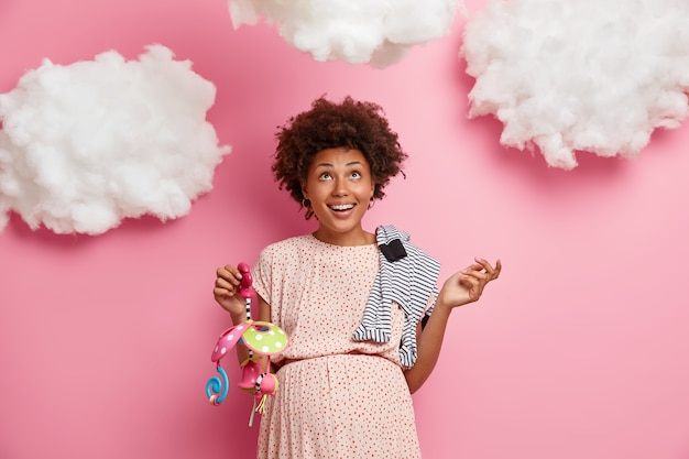 Image of happy pregnant woman poses with baby mobile and romper on shoulder, cannot wait for birth of child, has maternity feelings, looks above on white clouds. expectant mom with items for newborn