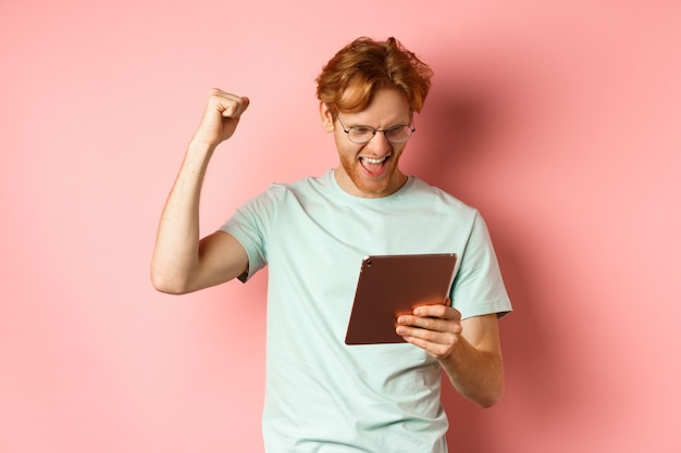 Image of happy redhead man triumphing winning online with digital tablet and rejoicing standing over...