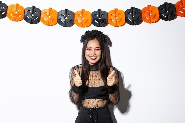 Immagine della femmina asiatica felice e soddisfatta in costume della strega che mostra il gesto eccellente, pollice in su e sorridere soddisfatto, stante contro la bandiera delle zucche.