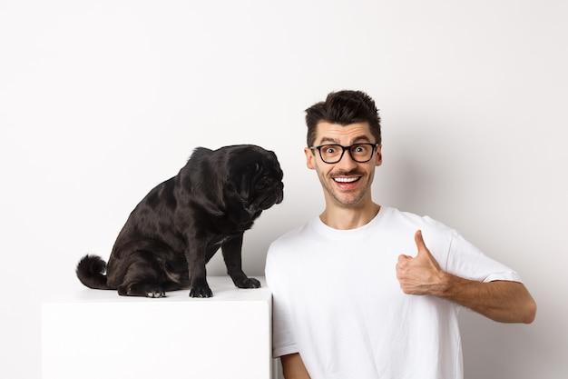 Immagine di un giovane felice e soddisfatto seduto vicino a un cane carlino e che mostra pollice in su, sorridente e lodando un buon prodotto, sfondo bianco