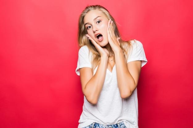 Immagine di felice urlando sorpreso giovane donna in piedi isolato su sfondo rosso. guardando da parte.