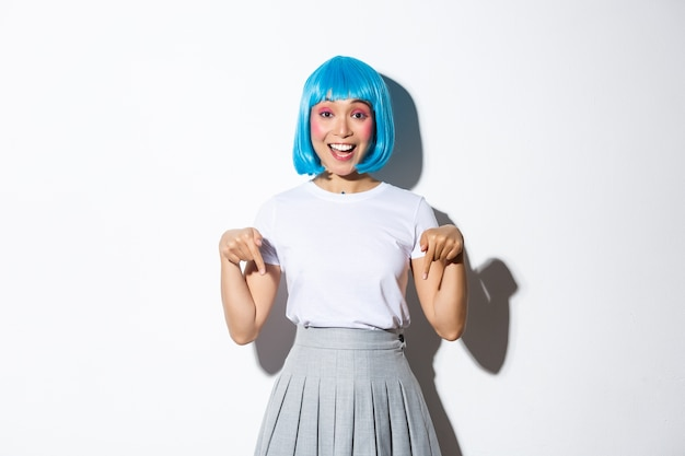 Image of happy silly asian girl showing you logo or product advertisement, pointing fingers down and smiling, wearing blue short wig, standing.