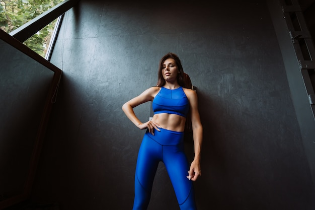 Image of happy sports young girl standing and posing over black wall. looking at camera. female resting after fitness.