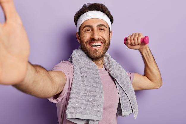 L'immagine dello sportivo felice ha allenamento al coperto, fa selfie con manubri