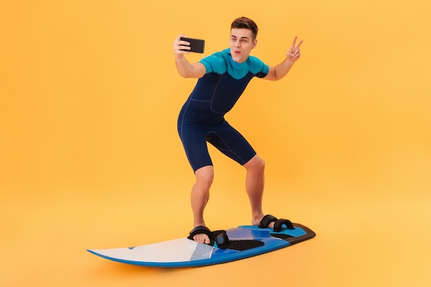 Image of happy surfer in wetsuit using surfboard like on wave while making selfie on smartphone and showing peace gesture