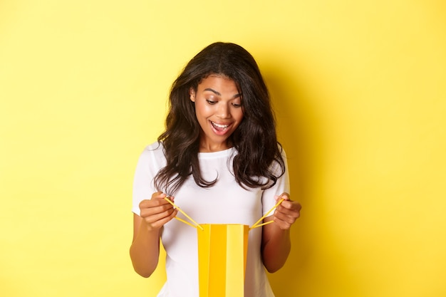 Image of happy and surprised african-american girl, receiving a gift, looking inside shopping bad with amazement, standing over yellow background