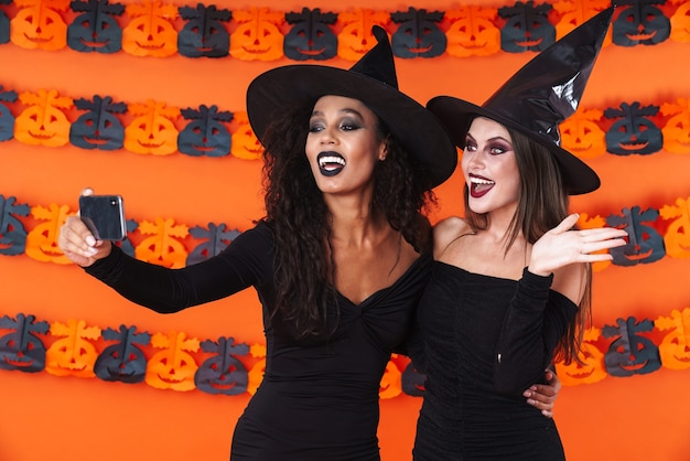 Image of happy witch women in black halloween costume taking selfie photo on cellphone with smiling isolated on orange pumpkin wall