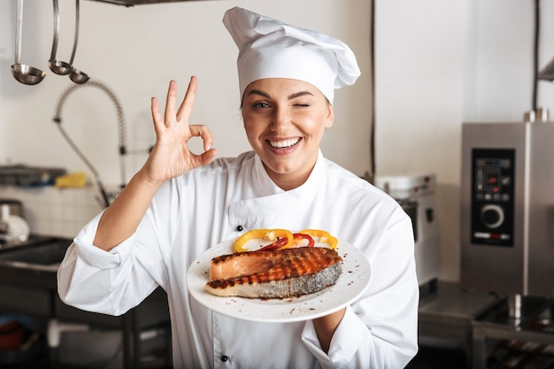 Image of happy woman chef wearing white uniform, holding plate with grilled fish in kitchen at the restaurant