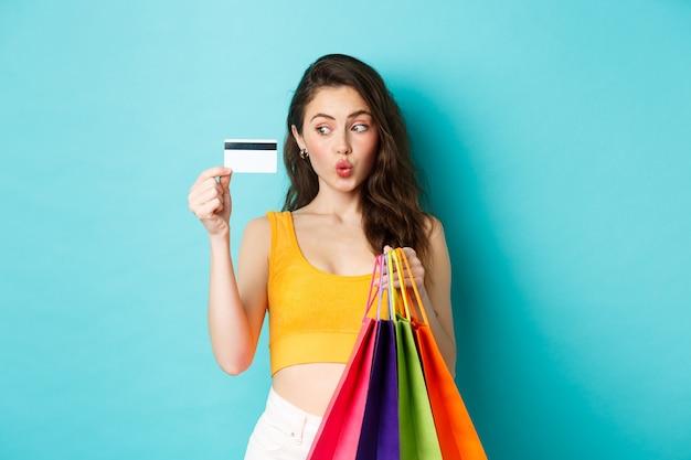 Immagine di una donna felice dello shopping che mostra la sua carta di credito in plastica, tiene in mano le borse della spesa, indossa abiti estivi, in piedi su sfondo blu.