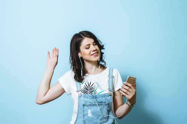 Image of happy woman wearing earphones singing isolated over blue wall