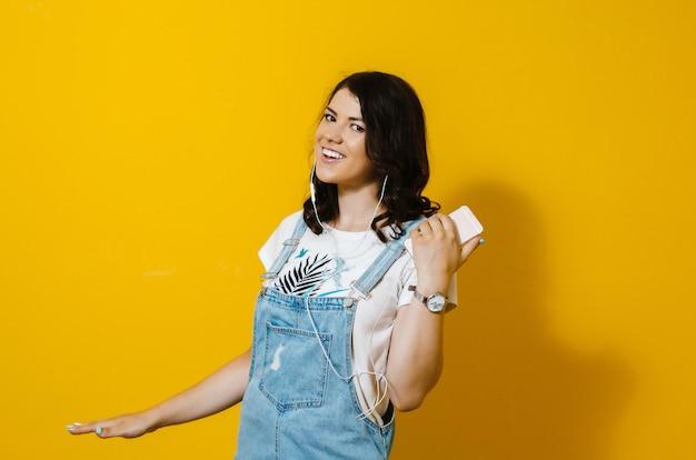 Image of happy woman wearing earphones singing isolated over yellow wall