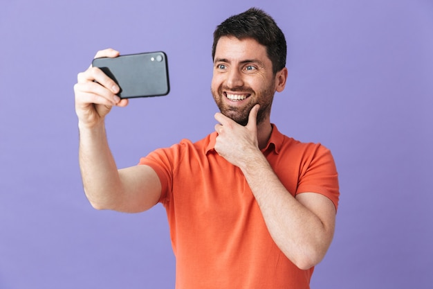 Image of a happy young handsome bearded man posing isolated over violet purple wall take selfie by mobile phone.