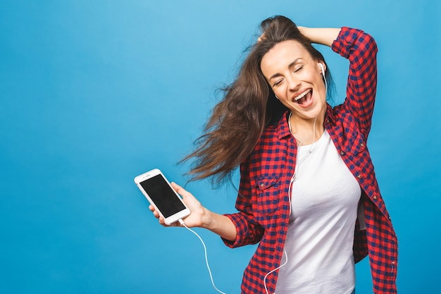 Image of happy young lady listening music in headphones