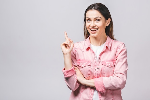 Image of happy young lady standing isolated over white background. looking camera pointing.