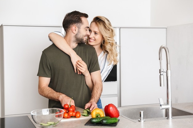 Image of a happy young loving couple posing at the kitchen at home cooking have a breakfast hugging.