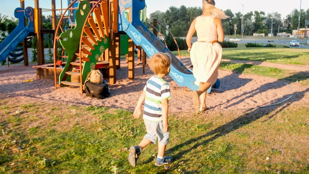 Image of happy young mother with 3 years old little son playing and running on the children playground at park
