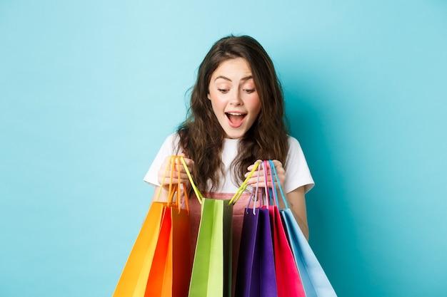 L'immagine di una giovane donna felice porta molte borse della spesa, compra cose su sconti primaverili, in piedi su sfondo blu.