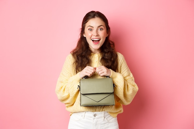 Image of happy young woman going on shopping, holding her purse and smiling excited, ready to go, standing against pink wall