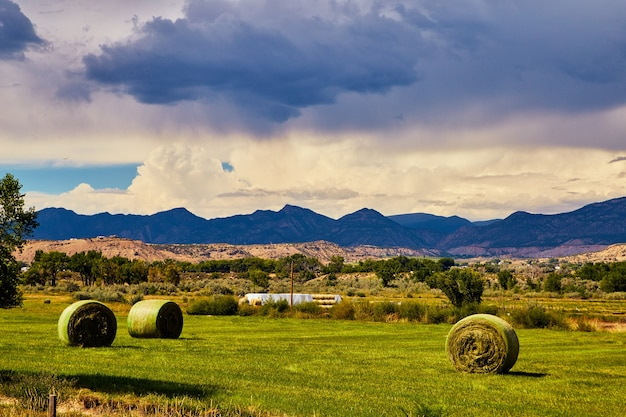 Image of hay bales in field with dark mountain silhouette and storm in background